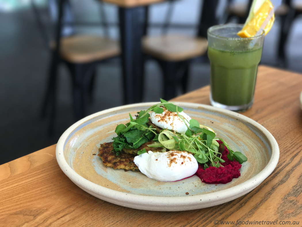 Zucchini fritters with beetroot hummus, poached eggs, dukkah, sautéed kale and cucumber ribbons