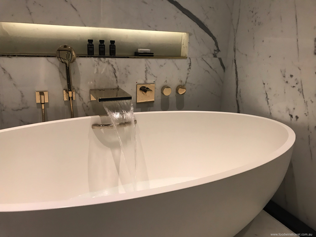 The sumptuous bathroom with marble walls and gold fittings.