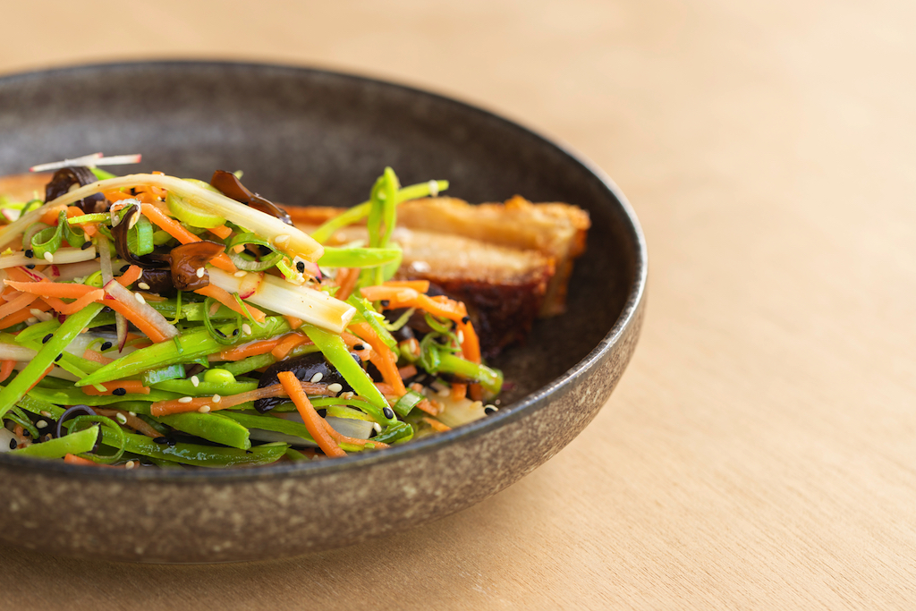 Roast pork belly with a pickled salad of snow peas, carrot, fungi and orange dressing.