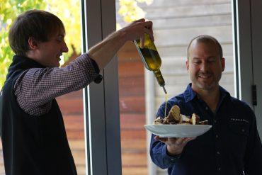 Primo Estate's Matteo Grilli pouring oil for cellar door manager, Mark Van Gestel, at the Estate's 2018 olive harvest celebration.