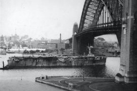 The Royal Navy aircraft carrier HMS Vindex passing under the Sydney Harbour Bridge with 300 ex-prisoners of war returning home. (Source: City of Sydney Archives)